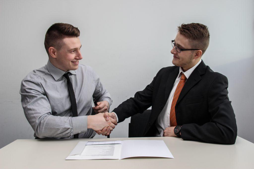 2 hommes se serrent la main en entrevue